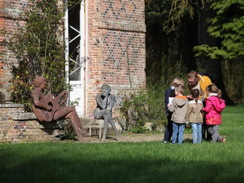 Un adulte faisant la visite des jardins de Bois-Guilbert a un groupe d'enfant