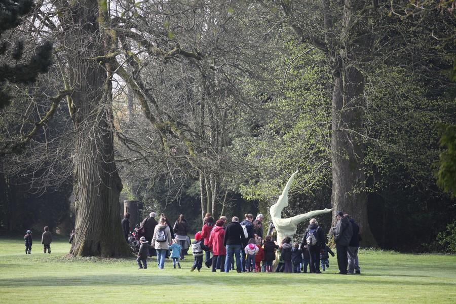 Groupe d'adultes accompagnés d'enfant visitant les jardins du château de Bois-Guilbert